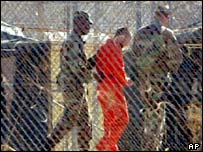 A prisoner, in an orange jumpsuit, is led by US military police at Camp X-Ray, Guantanamo Bay, Cuba