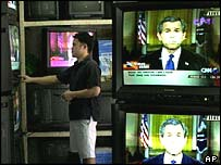 A TV store attendant watches a broadcast by President Bush