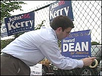 Campaign worker puts up posters for Howard Dean with others for John Kerry visible
