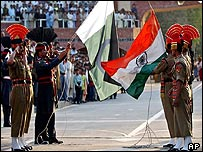 Pakistani soldiers [left] with Indian soldiers [right] lower flags at the countries' border