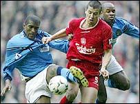 Milan Baros (centre) fends over City's Sylvain Distin (left) and David Sommeil
