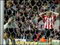 Jussi Jaskelainen looks on as Brett Ormerod rues a missed opportunity