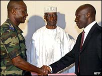 General Mathias Doue (l), Ivory Coast national army chief shakes hands with rebel leader Colonel Michel Gueu