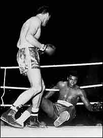 CASSIUS CLAY IS BEATEN TO THE FLOOR IN THE FOURTH ROUND AGAINST BRITISH HEAVYWEIGHT CHAMPION HENRY COOPER