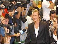 David Beckham and wife Victoria walk past a wall of cameras and reporters upon arrival  in Tokyo