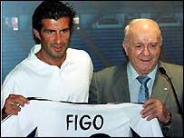 Luis Figo holds up the Real Madrid shirt he will be wearing next season next to legendary former Real Madrid player Alfredo de Stefano