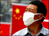 A man wears a protective mask near a line of Chinese flags 4 May 2003 in Shanghai