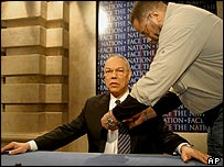 An audio technician places a microphone on Colin Powell on the set of Face the Nation, 4 May 2003