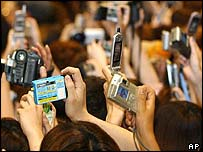 Thousands of young Japanese wait to get a photo of the England captain