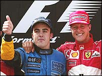 Fernando Alonso celebrates on the podium with Michael Schumacher