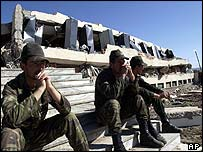 Soldiers sit next to the flattened dormatory