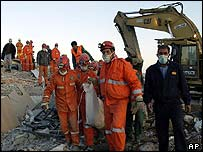 Rescue workers remove the last body from the rubble