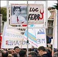 Protesters carry a banner denouncing education Minister Luc Ferry