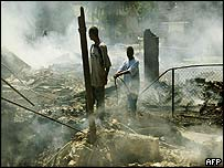 Two boys stand amid the smouldering remains of a neighbour's home 18 June, 2003 in Benton Harbor, Michigan