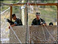 Armed military police watch detainees from a watchtower at Camp X-Ray at the U.S. Naval Base in Guantanamo Bay