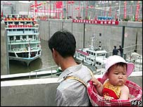 A man carrying his baby watches as a passenger ship passes through the permanent ship locks of the Three Gorges Dam