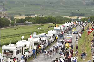 Caravans line the side of the road as the peloton rides past on stage four