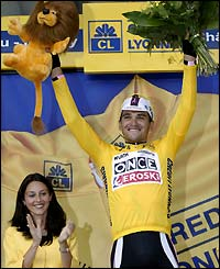 Oscar Gonzalez de Galdeano poses on the podium in the overall leader's yellow jersey after stage four