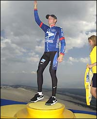 Lance Armstrong steps up onto the podium to receive the yellow jersey for the first time in 2002