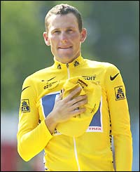Lance Armstrong puts his hand on his heart as he listens to the American national anthem after winning the Tour de France