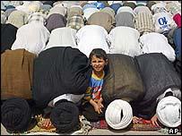 A boy looks up as men pray around him