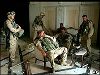 U.S. Army Stf. Sgt. Chad Touchett, centre, relaxes with comrades from A Company, 3rd Battalion, 7th Infantry Regiment, following a search in one of Saddam Hussein's palaces damaged after a bombing,