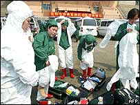 Chinese health workers don protective suits