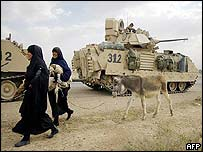 Iraqi women pass US military vehicles
