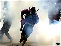 Protester runs from tear gas in nearby Greek town of Neos Marmaras
