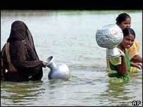 Bangladeshi women wading through flood water