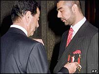 Saddam Hussein awards a medal to his son Uday