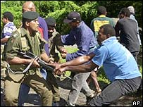 Fiji government soldiers struggle with supporters of rebel leader George Speight in Fiji during 2000 coup