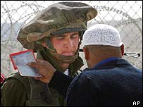 Israeli soldier checks Palestinian man's pass at checkpoint