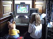 Girl sitting at computer with toy