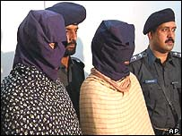 Police present two of the five suspects, in hoods, to the media