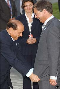 Mr Berlusconi pulls the jacket of the Dutch prime minister