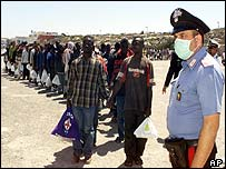 A Sicilian police officer stands in front of a queue of new arrivals