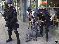 Officer in Sacramento stands guard as a protester is arrested