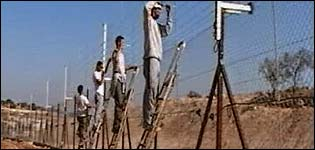 Workers construct the security fence
