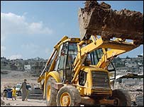 Bulldozer at work in Jenin as family walks past