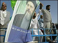Supporters wave a portrait of Ayatollah Hakim in Basra
