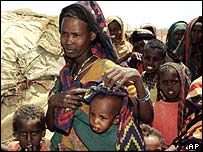A woman and children queue at a feeding centre