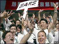 Beijing shop assistants celebrate outside their shop after the WHO announcement