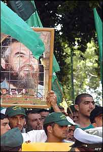 Israeli Arab protesters outside a Haifa courthouse wave green Islamic banners and carry a picture of Sheikh Raed Salah