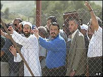 Palestinians wait behind a fence for their documents to be checked by Israelis at the entrance to the northern West Bank town of Nablus