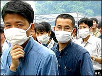 People wear masks on a crowded street in Guangzhou