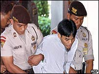 Amrozi is being escorted by police into a court room in Denpasar