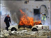 Observers walk past a flaming car at the beginning of a terrorism response exercise Monday, May 12, 2003, in Seattle