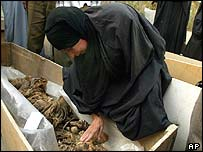 Woman touches the remains of her son found in Basra mass grave