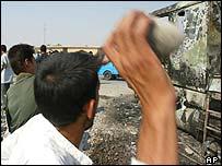 Iraqi man throws rock at attacked US convoy